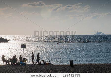 Dor Beach, Israel / 18 Oct 2019: Beachgoers Relaxing On Beach In Front Of Environmentally Controvers