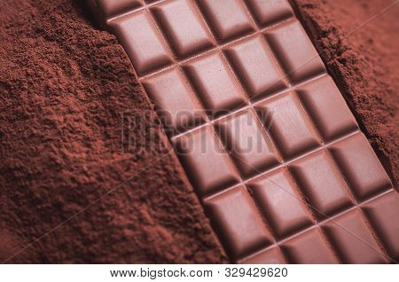 Above View Of Chocolate Bar On A Pile Of Cocoa Powder. Cooking Background With Chocolate Dessert Ing