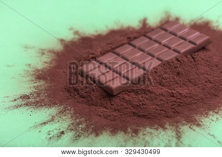 Close-up Of Chocolate Bar And Cocoa Powder Pile On Green Background. Whole Milk Chocolate Bar On Cac