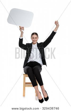 good looking businesswoman wearing black suit sitting and holding speech bubble with enthusiasm against white studio background