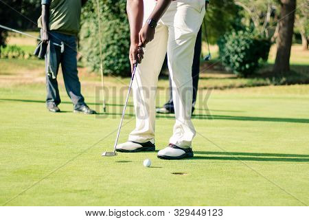 Male Lower Body In White Pants Making Golf Putt