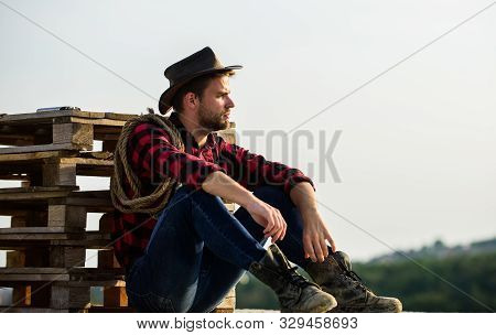 Romanticism Of Western Culture. Farmer In Hat Sit Relax. Farmer Enjoy View From His Farm. Peaceful M