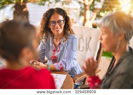 Meeting of middle age women having lunch and drinking coffee. Mature friends smiling happy using smartphone at home on a sunny day