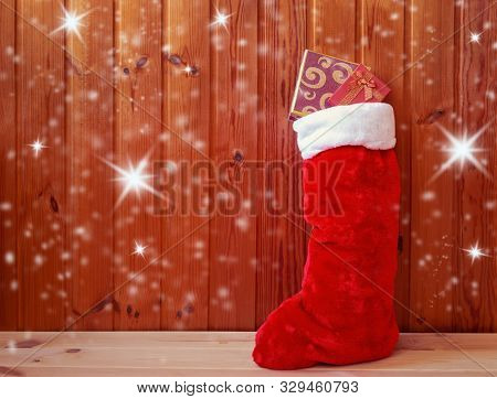Christmas Fluffy Stocking Standing Near Wooden Wall. View With Copy Space.