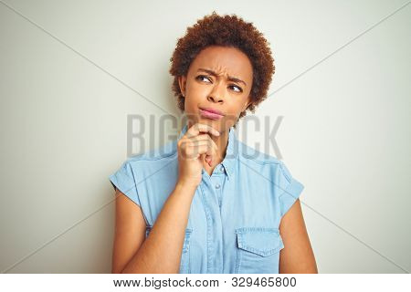 Young beautiful african american woman with afro hair over isolated background with hand on chin thinking about question, pensive expression. Smiling with thoughtful face. Doubt concept.