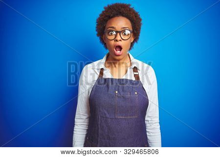 Young african american woman shop owner wearing business apron over blue background afraid and shocked with surprise expression, fear and excited face.