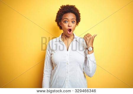African american business woman over isolated yellow background Surprised pointing with hand finger to the side, open mouth amazed expression.