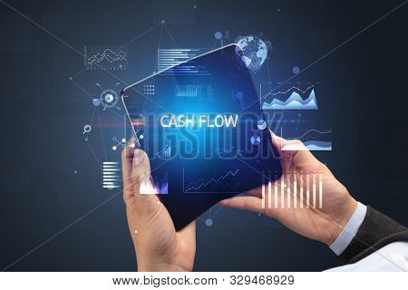 Businessman holding a foldable smartphone with CASH FLOW inscription, successful business concept