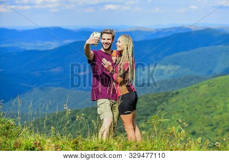 Couple taking photo. Summer vacation concept. Young adventurers. Travel together with darling. Couple in love hiking mountains. Lets take photo. Capturing beauty. Man and woman posing mobile photo poster