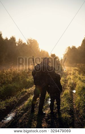 Rifle Hunter And His Son Silhouetted In Beautiful Sunset. Huntsman With A Boy And Rifle In A Forest