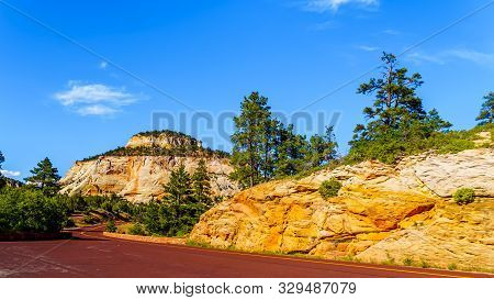 The Red Colored Pavement Of Zion-mt.carmel Highway As It Winds Through The White Sandstone Mountains