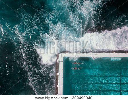 Dramatic Birds Eye View Of Ocean Waves Crashing Against Infinity Pool At Bondi Beach, Sydney Coastal