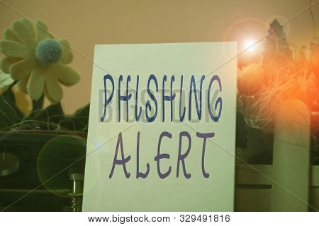 poster of Handwriting text Phishing Alert. Concept meaning aware to fraudulent attempt to obtain sensitive information Flowers and writing equipments plus plain sheet above textured backdrop.