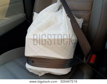 Plastic Bag With Take Out Or Delivery Or To Go Food In Seatbelt In Car