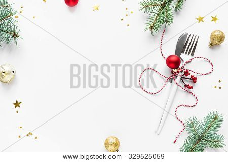 Christmas Table Setting With Fir Branch And Red Ornaments On White, Flat Lay, Copy Space. Christmas