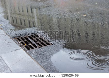 Autumn Asphalt, Metal Grating Stormwater On A City Street. Autumn Rainy Weather With Puddles, Outflo