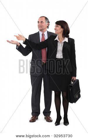 Mature businesscouple gesturing at blank copyspace