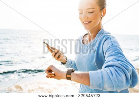 Photo of a happy fitness woman running outdoors on beach using mobile phone listening music with earphones looking at watch clock.