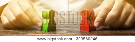 A Man Holds In His Hands The Red And Green Figures Of People Facing Each Other. The Search For A Com