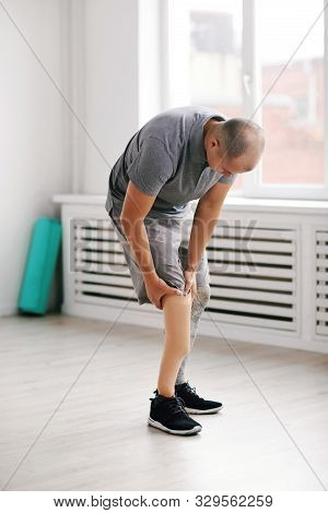 Young Man Standing In The Room And Touching His Prosthesis Leg