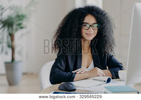 Positive Female Director With Afro Curly Hair, Rewrites Information In Notepad From Computer, Wears