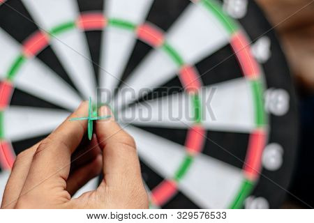 Dart On Hand Before Trowing To Get Win On Dartboard Target Business And Idea Concept