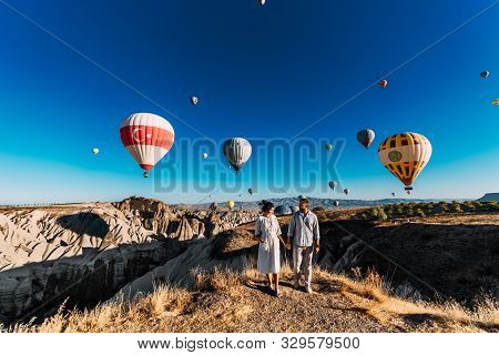 Couple In Love Stands On Background Of Balloons In Cappadocia. The Couple Travels The World. Vacatio