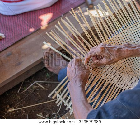 A skillful elderly handicapped man do bamboo wickerwork by hands on the floor. Showing simply way of life by self- reliance practice. poster