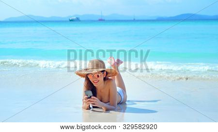 Happy Asian Woman, A Sexy Thai Lady, Using A Mobile Smartphone At Turquoise Sea Near Phuket Beach In