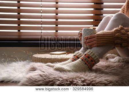 Woman With Cup Of Hot Drink Wearing Knitted Socks On Window Sill Indoors, Closeup. Warm Clothes