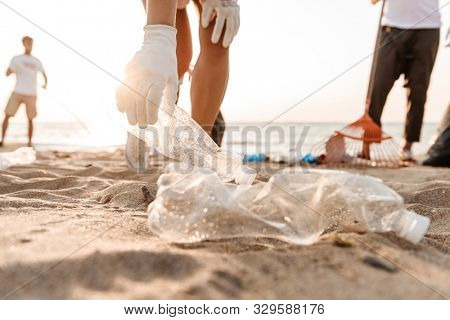 Group of young friends volunteers cleaning beach from plastic garbage