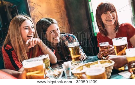 Happy Women Best Friends Drinking Beer At Vintage Bar Restaurant - Female Friendship Concept With Yo