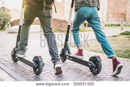 Close Up Of People Couple Using Electric Scooter In City Park - Millenial Students Riding New Modern
