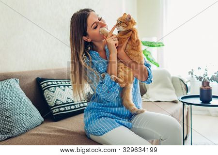 Playing With Cat At Home. Young Woman Sitting On Couch Teasing And Hugging Pet.