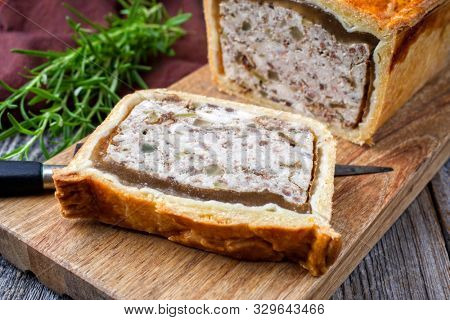 Traditional French Pate en croute with chicken offered as closeup on a modern design cutting board