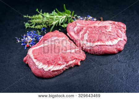 Traditional German raw beef cheeks offered as closeup on a black board with copy space