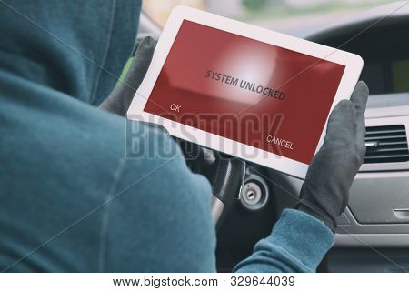 Hooded thief tries to break the car's security systems with tablet. Hacking modern car concept