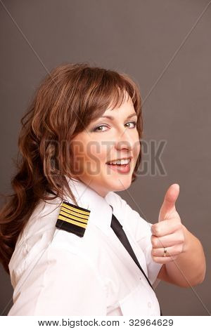 Beautiful airline pilot wearing uniform with epauletes showing thumb up gesture of approval