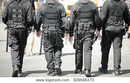 Four Policemen With Anti-riot Uniform Patrolling The City