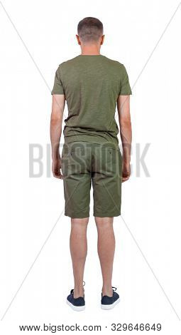Back view of young manin shorts looking. Rear view people collection. backside view of person. Isolated over white background. A guy in summer clothes looks into the distance.