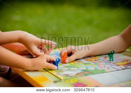 Family Playing A Board Game, One Kid Is On The Move And Capturing The Piece Of Another Player.games