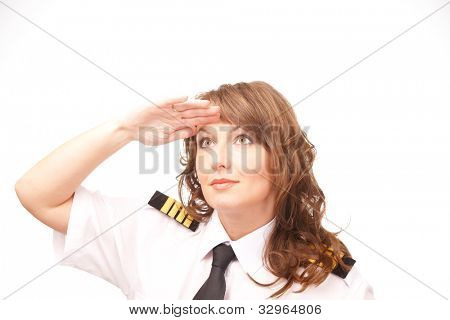 Beautiful woman pilot wearing uniform with epauletes looking ahead, standing isolated on white background.