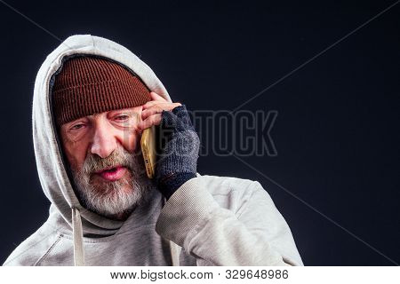 Portrait Of Sad Old Senior Male Tramp Wearing Warm Brown Hat And Leaky Gloves, Talking By Smartphone