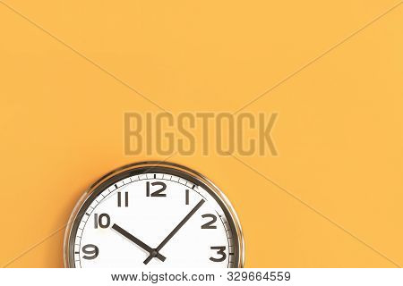 Time Concept. Part Of White Wall Clock On Trendy Pastel Orange Background. Close Up With Copy Space,