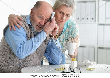 Portrait Of Sick Senior Couple Calling To Doctor