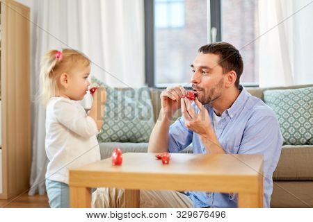 family, fatherhood and childhood concept - happy father and little daughter with toy crockery playing tea party at home poster