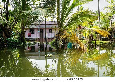 Traditional House In The Kerala Backwaters In The Lush Jungle Along The Canal With Bright Reflection