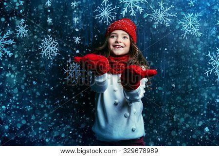 A portrait of a pretty young girl wearing in warm clothes and accessories. Winter fashion for kids, beauty.