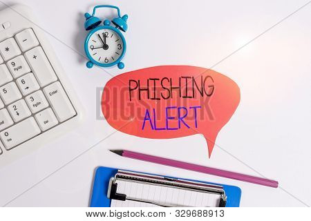poster of Word writing text Phishing Alert. Business concept for aware to fraudulent attempt to obtain sensitive information Flat lay above table with clock pc keyboard and copy space note paper.