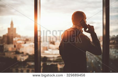 Silhouette Of A Prosperous Man Entrepreneur Standing Near The Panoramic Window Of A Luxurious Busine